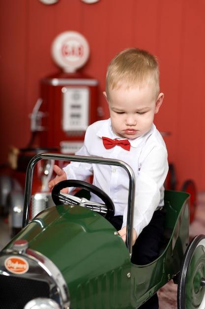 Leuke peuter speelt met speelgoedauto's. rijdt op een speelgoedmachine met typemachine. gelukkige jeugd Premium Foto