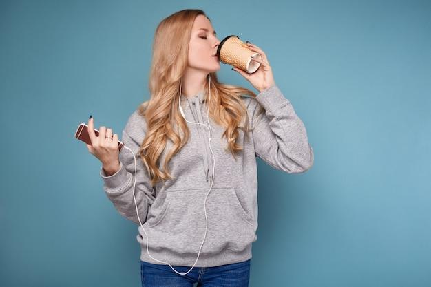 Leuke positieve blondevrouw in hoodie met telefoon en koffie Premium Foto