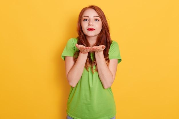 Leuke romantische roodharige vrouw permanent en verliefd lucht kus verzenden naar camera, genegenheid tonen, groene t-shirt dragen Gratis Foto