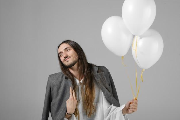 Leuke stijlvolle jongeman met baard en lang losse haren poseren met drie witte helium ballonnen, verjaardag vieren Gratis Foto