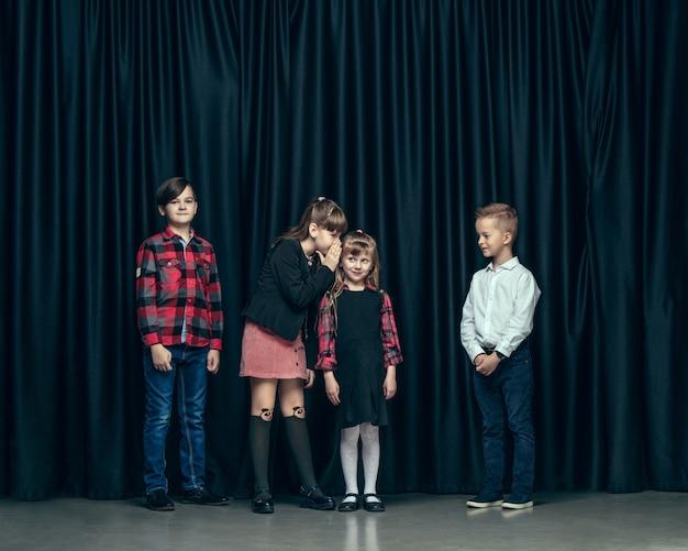 Leuke stijlvolle kinderen op donkere studio. de mooie tiener meisjes en jongen staan samen Gratis Foto