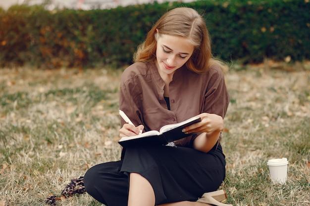Leuke student die in een park werkt en het notitieboekje gebruikt Gratis Foto