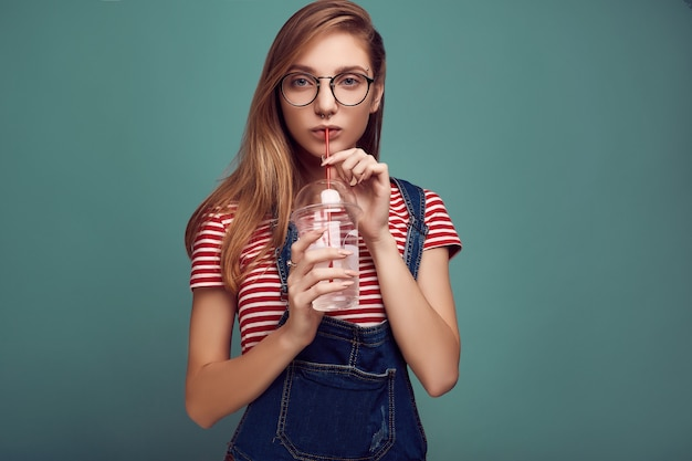 Leuke tiener in denimoverall en glazen met sodawater Premium Foto