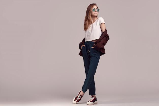 Leuke tiener in mode jas en kleur bril Premium Foto