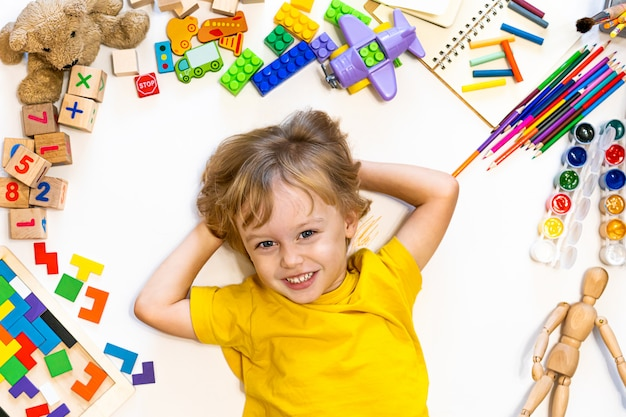 Leuke voorschoolse lachende jongen tekenen en spelen met blokken, vliegtuig en auto's. Premium Foto