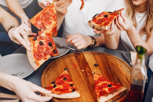 Leuke vrienden in een koffie die een pizza eatting Gratis Foto
