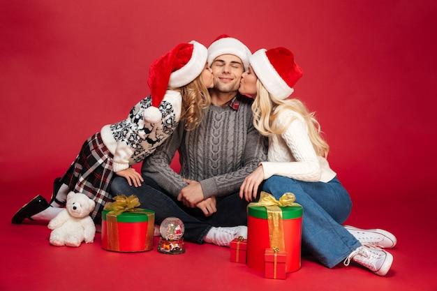 Leuke vrolijke jonge familie die kerstmishoeden geïsoleerd zitten dragen Gratis Foto
