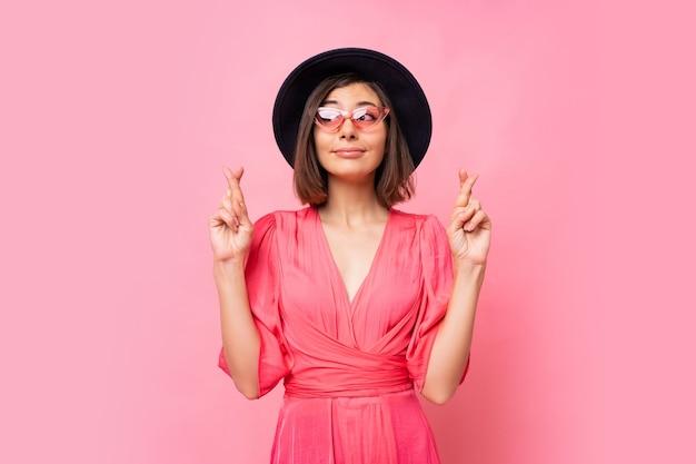 Leuke vrolijke vrouw wil haar best doen om haar vingers gekruist te houden, heeft het beste, gekleed in jurk geïsoleerd op een roze muur. mensen, lichaamstaal concept. copyspace. Gratis Foto