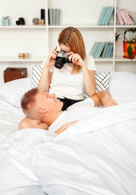 Leuke vrouw die een foto van haar vriend in bed neemt Gratis Foto