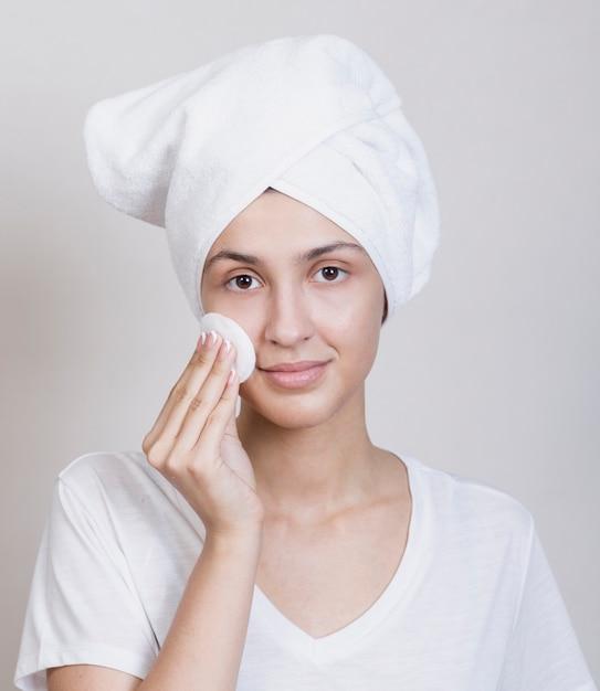 Leuke vrouw die haar gezicht schoonmaakt Gratis Foto