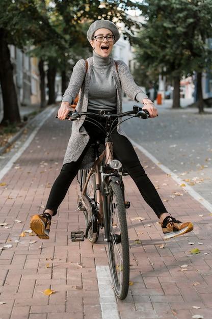 Leuke vrouw gek rond op haar fiets Gratis Foto