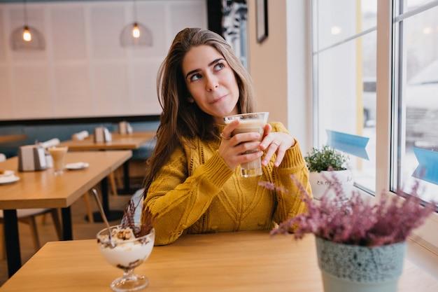 Leuke vrouw in trendy gele trui iets na te denken tijdens het rusten in café met glas cappuccino. indoor portret van prachtige dame wachten op vriend en genieten van ijs. Gratis Foto