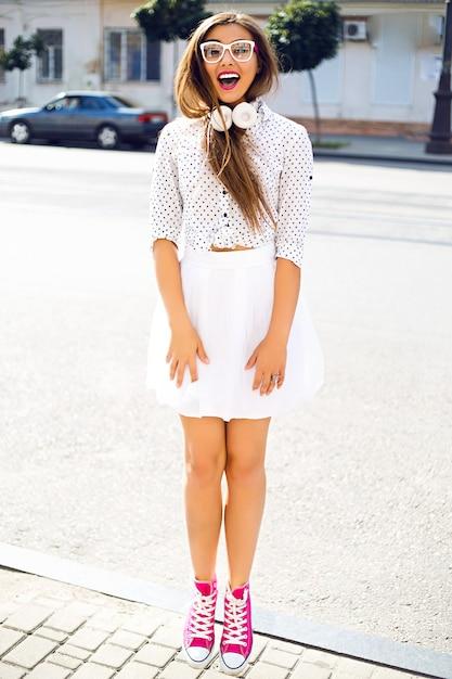 Leuke vrouw met plezier op straat, gekleed in witte grappige jurk en witte koptelefoon Gratis Foto