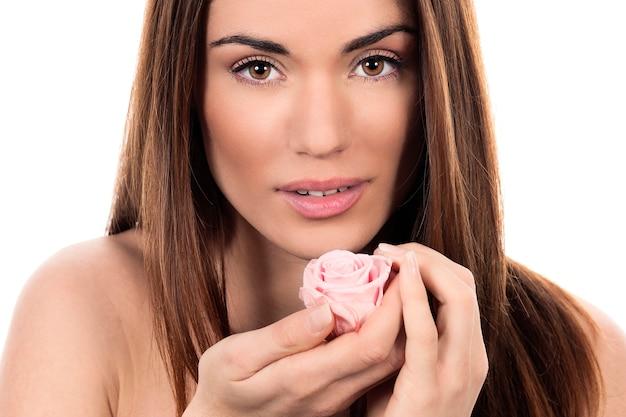 Leuke vrouw met roze roos op witte achtergrond Gratis Foto