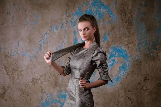 Leuke vrouw poseren in een jurk op een grunge muur Gratis Foto