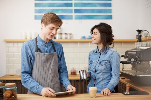 Leuke vrouwelijke barista die rafkoffie maakt die vrolijk glimlacht, er gelukkig uitziet. Gratis Foto