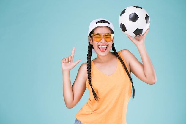 Leuke vrouwenfan van voetbalkampioenschap. fit meisje houdt bal over blauwe achtergrond. Premium Foto