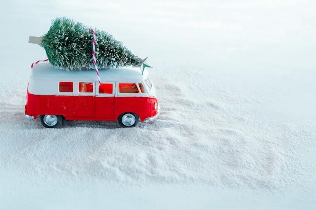 Leuke winter vakantie wenskaart kerstboom op retro speelgoed vrachtwagen in besneeuwde bos Premium Foto