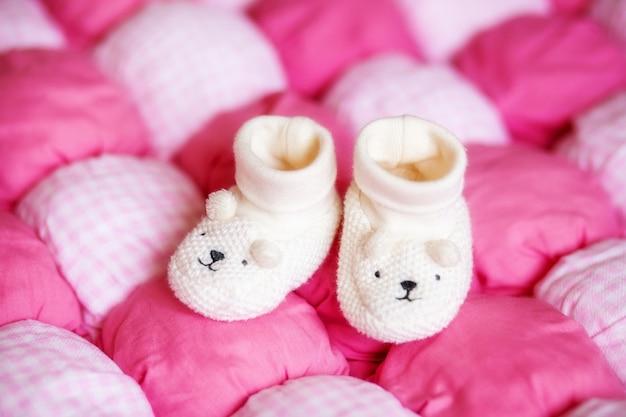 Leuke witte babybuiten op roze deken. zwangerschap concept Premium Foto