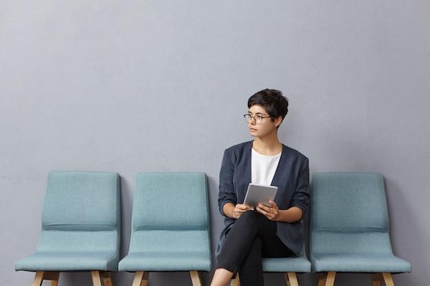 Leuke zakenvrouw kijkt peinzend opzij, wacht op ontmoeting met partners Gratis Foto