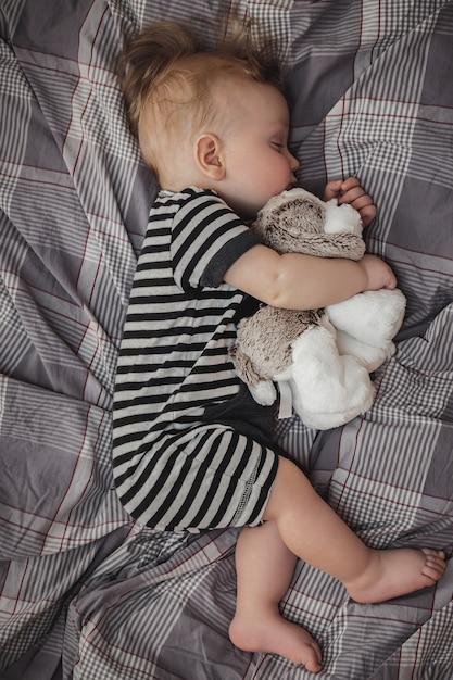 Leuke zes maanden oude blonde jongen die op een grijs bed met een stuk speelgoed in zijn handen slaapt Premium Foto