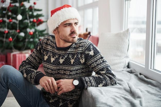 Leunend op de vensterbank. foto van de mens in kerstmuts en vakantie kleding kijkt door het raam. kerstboom op achtergrond Premium Foto