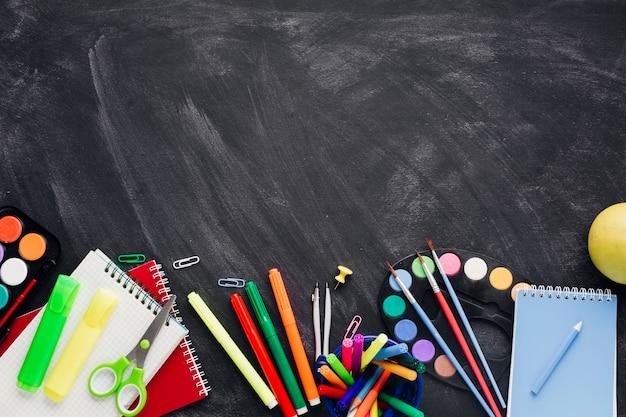 Levendige creatieve briefpapier en -laptops op een grijze achtergrond Gratis Foto