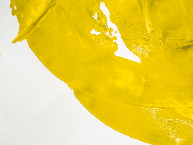 Levendige gele verf op wit canvas Gratis Foto