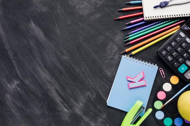 Levendige kantoorbehoeften met notitieboekje, calculator en verdeler op donkere achtergrond Gratis Foto