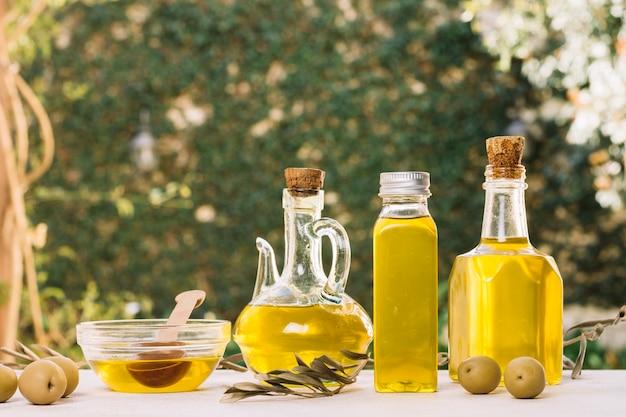 Levendige olijfolieflessen buitenshuis Gratis Foto