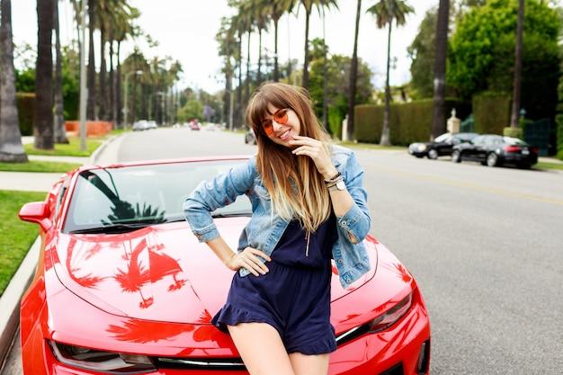 Levensstijl afbeelding van reizen vrouwelijke zittend op de motorkap van geweldige rode cabriolet sportwagen. straten van los angeles Gratis Foto