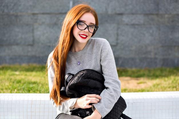 Levensstijl buiten portret van vrij gember meisje helder glas en kasjmier grijze trui dragen, poseren in het park, herfst winter stijl. met een rugzak. Gratis Foto