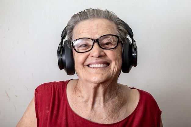Levensstijl en mensenconcept: grappige oude dame het luisteren muziek en het dansen op witte achtergrond. bejaarde die glazen draagt die aan muziek dansen die op zijn hoofdtelefoons luisteren. Premium Foto
