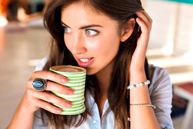 Levensstijl indoor portret van jonge brunette vrouw die zich voordeed op stadscafetaria genieten van haar lekkere warme koffie in de ochtend Gratis Foto