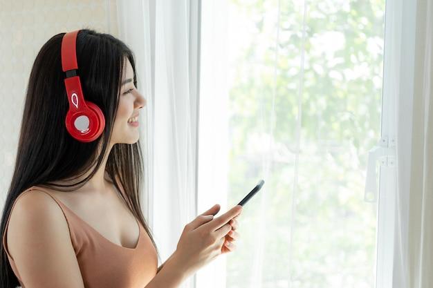 Levensstijl mooie aziatische vrouw schattig meisje voelt gelukkig genieten van het luisteren naar muziek met koptelefoon koptelefoon op witte slaapkamer Gratis Foto
