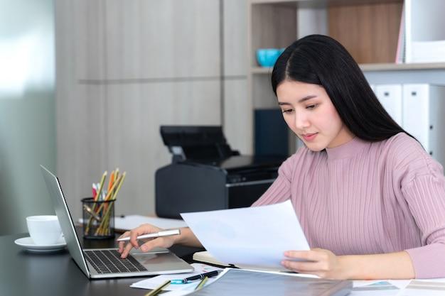 Levensstijl mooie aziatische zakelijke jonge vrouw met laptopcomputer en slimme telefoon op kantoor Gratis Foto