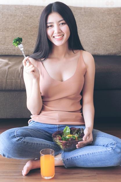 Levensstijl mooie schoonheid vrouw aziatische schattig meisje voelt gelukkig genieten van het eten van dieet eten frisse salade en sinaasappelsap voor een goede gezondheid in de ochtend Gratis Foto