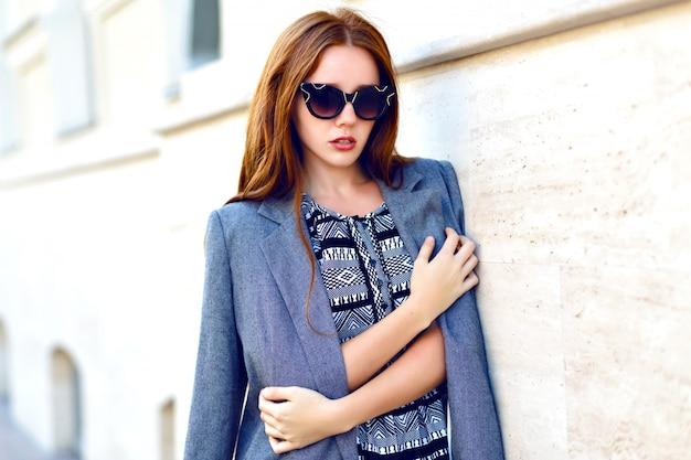 Levensstijl portret van vrouw, elegante glamour jas jurk en vintage zonnebril, afgezwakt warme kleuren, positieve stemming dragen. Gratis Foto