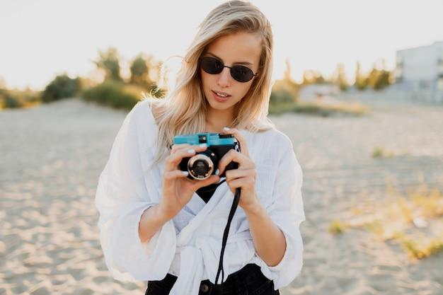 Levensstijl positief beeld van stijlvol blond meisje met plezier en het maken van foto's op een leeg strand. vakantie en vakantietijd. vrijheid en natuur op het platteland. Gratis Foto