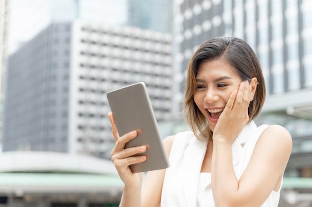 Levensstijl zakenvrouw voelen zich gelukkig met behulp van smartphone Gratis Foto