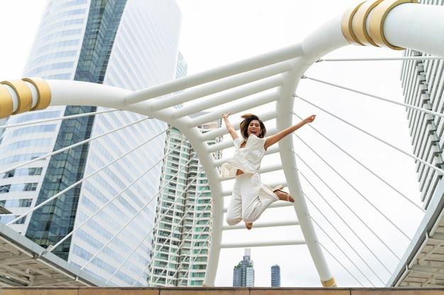 Levensstijl zakenvrouw voelen zich gelukkig springen in de lucht vieren van succes Gratis Foto
