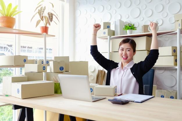 Levensstijlondernemers die in bureau zitten die het schermlaptop glimlachen glimlachen die, kleine onderneming kmo werken Premium Foto