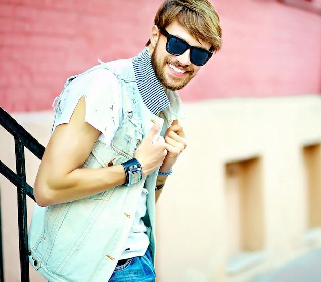 Levensstijlportret van grappige glimlachende hipster knappe mensenkerel in modieuze de zomerkleren die op straatachtergrond stellen in zonnebril Gratis Foto