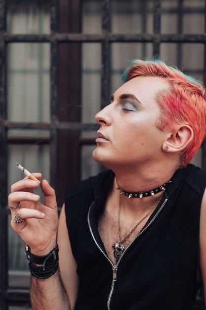 Levensstijlportret van homoseksuele rokende sigaret met tevreden gelaatsuitdrukking Premium Foto