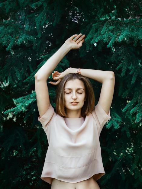 Levensstijlportret van jonge witte vrouw met kort haar die zich voor pijnboomboom bevinden met haar gesloten ogen en opgeheven handen Premium Foto