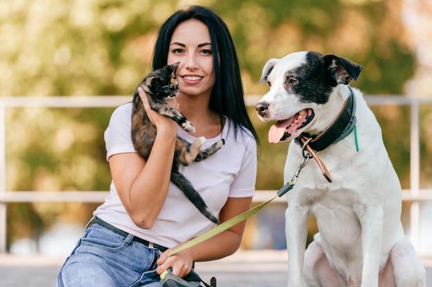 Levensstijlportret van mooi jong donkerbruin meisje met weinig kat en grote hondenhondzitting openlucht in park. gelukkige vrolijke glimlachende tiener die mooie huisdieren koestert. Premium Foto