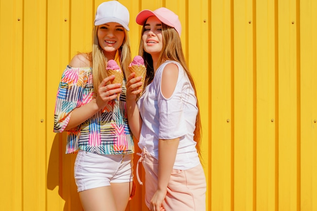 Levensstijlportret van twee mooie beste vrienden hipster dame die modieuze heldere uitrustingen dragen Premium Foto