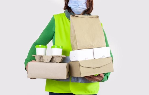 Lever in een groen vest met papieren dozen en een container om mee te nemen met twee witte kopjes koffie. Premium Foto