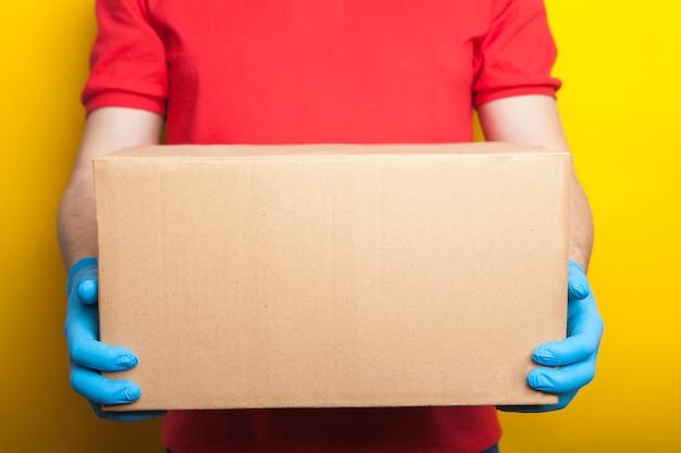 Levering aan huis, online bestelling. een man in uniform, een medisch masker en rubberen handschoenen met een doos, een pakje in zijn handen. Premium Foto
