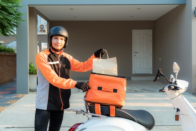 Levering aziatische man met oranje uniform en klaar om het verzenden van voedsel zak te sturen Premium Foto